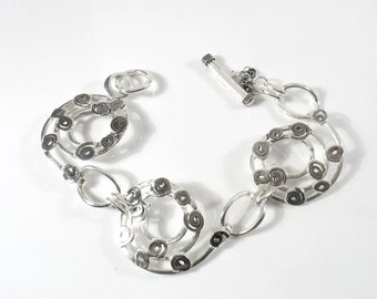 Oxidized small sterling spirasl on three larger spirals to create this funky bracelet.Our life is our spiral.