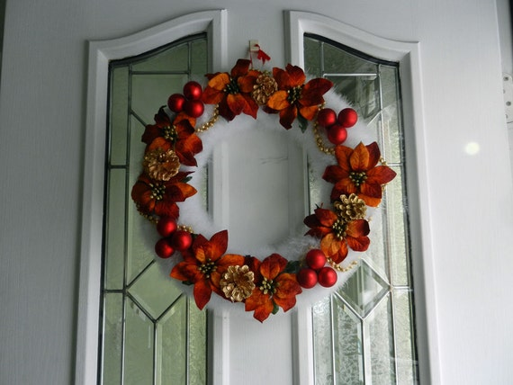 White Marabou wreath with rustic poinsettia flowers  red christmas balls and gold garland .