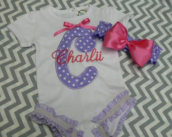 Baby Girl's Large Initial Applique Onesie With Name Monogrammed Across, Ruffle Around Legs with Mathching Fabric Headband and Satin Bow
