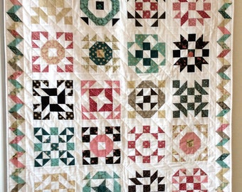 Sampler Quilt in pinks, brown, greens, beiges and snow lap size throw