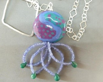 Jeweled Octopus Lariat loops a large Kenyan ceramic bead, tentacles of tanzanite tipped in emeralds, thru a silver diamond and circle chain