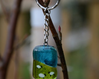 Gorgeous fused glass keyring. Blue skies and sheep grazing in the fields. Hand made.