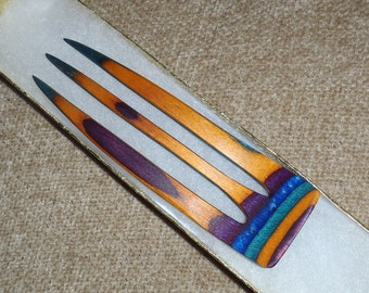 """3 prong wooden hair comb fork, 5 inches long, hand shaped of """"Gemwood"""" purple, blue teal, orange colored hardwood."""