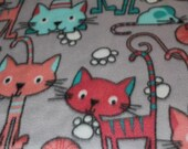 Handmade, soft, padded, fleece cat mat (with an opening for cat nip) featuring pink, peach and blue cats on a gray background