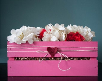 Pink crate with white hydrangea flowers