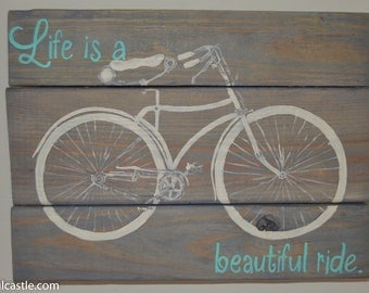 "Reclaimed wood sign with a hand-painted vintage style bicycle with the saying ""Life is a beautiful ride""."