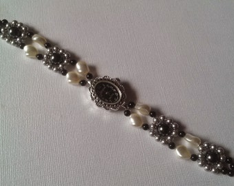 Decorative black and silver watch and a band of cream, light grey, black, and mystic black Swarovski crystal pearls. Rose clasp