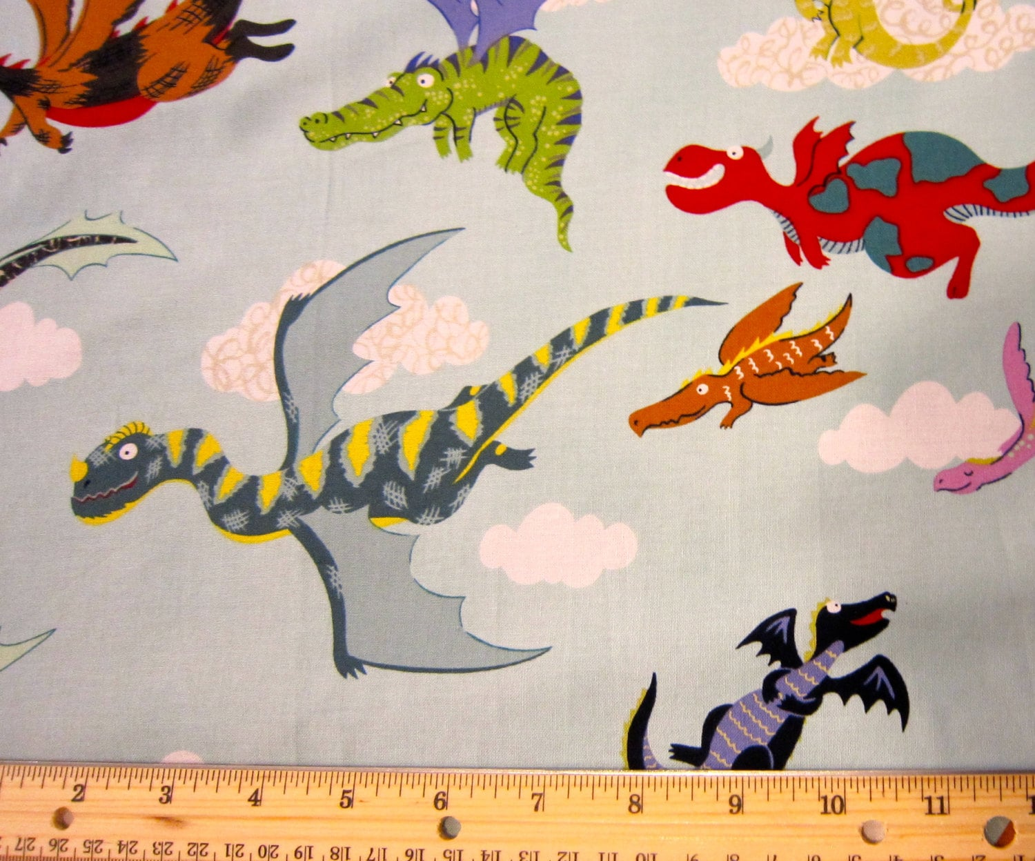 Dragon cotton fabric by alexander henry with aqua background for Dragon fabric kids