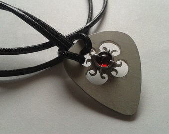 guitar pick with garnet stone