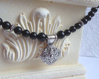 Black onyx beaded necklace with sterling silver floral pendant. Handforged sterling silver clasp.