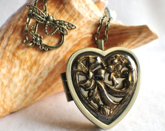 Music box locket,  heart shaped  locket with music box inside, in bronze with bow and flowers on front cover.