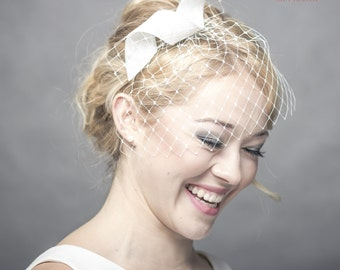 Modern curly wedding fascinator with delicate veiling, sinamay bow headpiece, ivory bridal headpiece