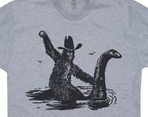 Bigfoot T Shirt Riding On Nessie Tee Funny T Shirts Loch Ness Monster Nessy Vintage Sea Creature Monster Shirts Believe Cool Graphic