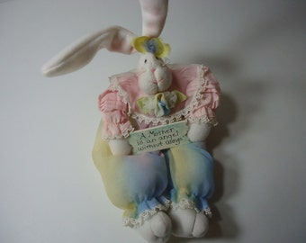 Bunny Doll  that sts and is 14 inches tall from top of ear to feet. Says a Mother is an angel with out wings