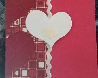 White and foil heart on red card