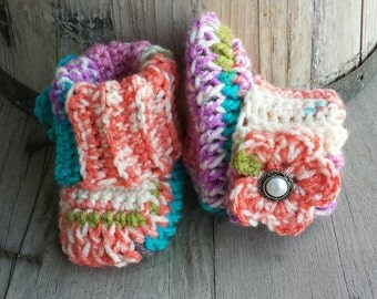 Crochet baby girl boots, with matching flower and pearl button center. size 0 to 3 mo.