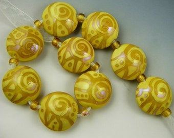 a set of 9 lentil beads in opal yellow and iridescent Aurae handmade lampwork glass - Cashmere