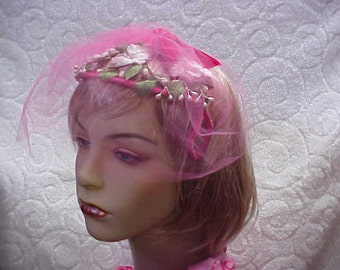 Pink flower headband style fascinator hat with pink face netting- spreads to fit