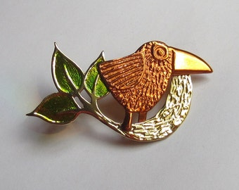 Small bird brooch with green leaves