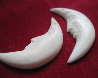 Two  hand carved half moon bone faces with holes on top.