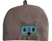 Cat in blue glasses, large teapot tea cosy in dusky pink
