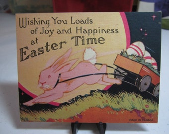 Art deco 1920's-30's colorful easter greeting card shows a pink easter rabbit harnessed to a cart pulling decorated easter eggs under moon