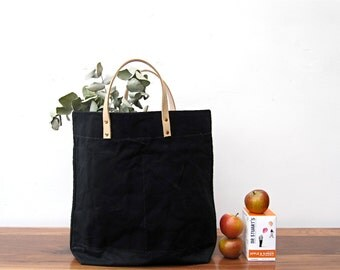 Black shopper. A washed canvas carrier bag with natural leather handles and brass details.