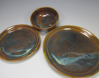 Three piece place setting. Brown, blue and maroon dinner set