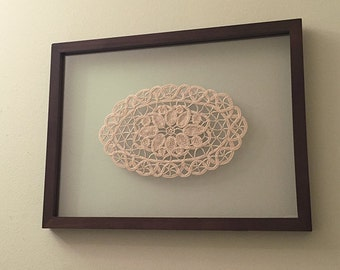 Vintage crocheted doily in a wood frame