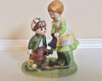 A Cute Figurine of a Mother  Helping Her Child Take off His Boots.