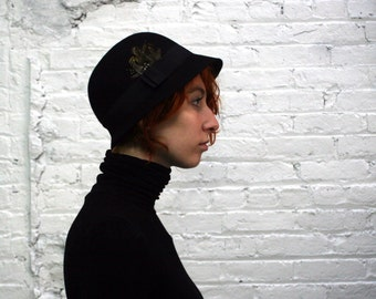 vintage 70s black wool felt cloche hat with feather and ribbon detail