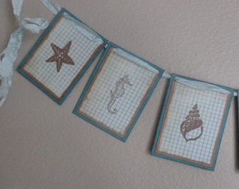 Beach themed garland or banner with seashells, handstamped, vintage style, teal and brown, cottage decor, nautical, lighthouse