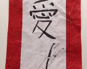 Love in Japanese Calligraphy on a red scroll