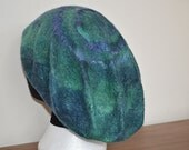Hand made peacock dyed merino wool and silk sliver hat, designed to mimic a seashell beret it is wet felted with a swirl pattern in silk