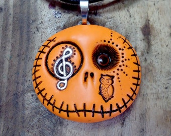 Orange happy skull keychain with a metal treble clef in his eye and a owl on his face. Pendant, brooch, keychain or magnet (choose)