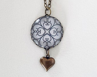 Metallic Silver Glass Dome Pendant with an Antiqued Brass Heart Dangle