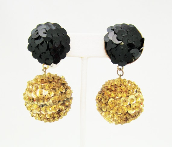 Black sequined clip-back earrings with heart-shaped drops, circa No maker's mark.