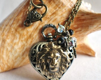 Heart watch locket in bronze with lion head mounted on front cover of watch.