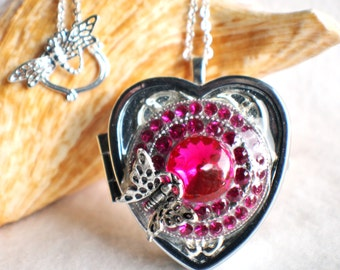 Music box locket, heart shaped locket with music box inside, in silver tone with pink rhinestones and butterfly on front cover.