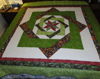 This Labryrinth quilt is made with vibrant green and red cotton fabrics.  It is approximately 102 x 85 inches.  shown on a king size bed.