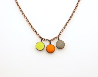 Handmade enameled necklace; dots of gray, yellow/green and orange are clad in antiqued copper cups.