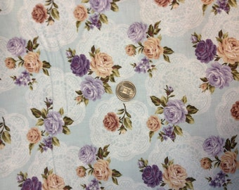 light blue background with lavender,tan, and purple flowers and white lacy look medium floral