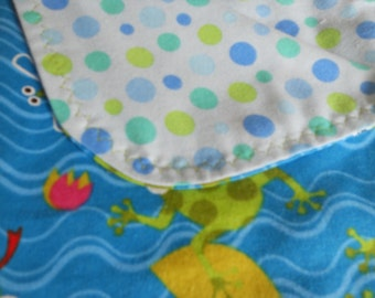Baby blanket with frogs in water on one side and blue and green dots on the other side.