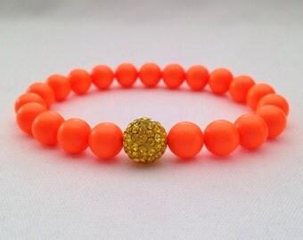 Orange neon bracelet with yellow Shamballa glitter ball, day glow orange bracelet, neon orange bracelet.