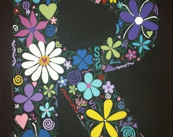 Handpainted letter on canvas with flowers, hearts, and things