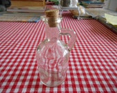 Vintage clear glass bottle with handle and cork on top