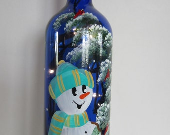 Snowman Standing Next to a  Whimiscal Winter Tree with Cardinals on a Blue Bottle