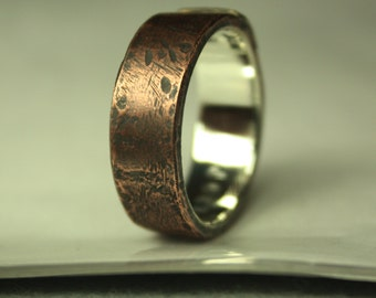 Artisan, rustic, organic copper/brass top layer. One-of-a-kind design for him. Plain polished sterling silver inside of the ring, no text.