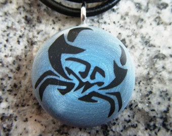Cancer Zodiac symbol hand carved on a polymer clay blue and grey pearl blend color background.  Pendant comes with a FREE 3mm necklace.