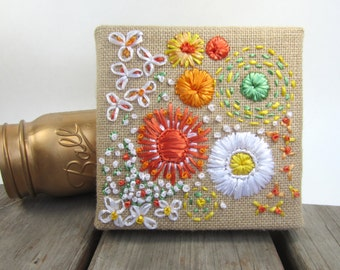 Abigale's flowers. Shades of orange, white, yellow and green vintage Swistraw embroidered flowers on burlap by Ruby Buffalo.